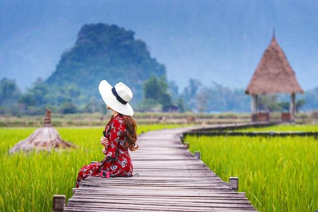 Junge frau, die auf hölzernem weg mit grünem reisfeld in vang vieng, laos sitzt.