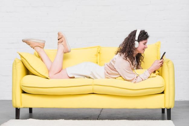 Junge frau, die auf hörender musik des gelben sofas auf kopfhörer liegt
