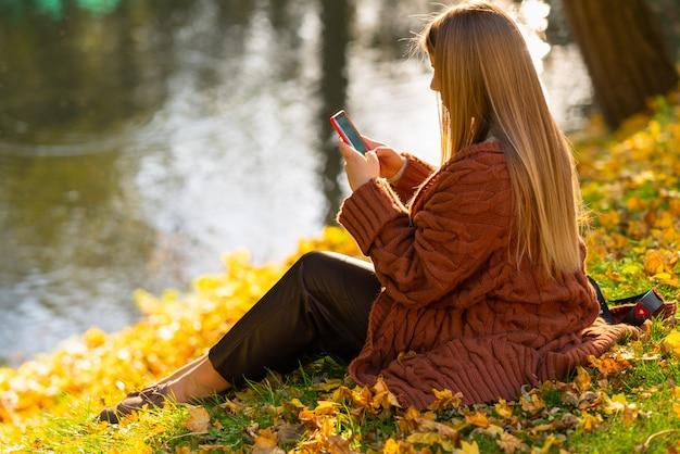 Junge frau, die auf ihrem handy eine sms schreibt, während sie sich am ufer eines sees in einem herbstpark mit bunten gelben herbstblättern auf dem gras entspannt