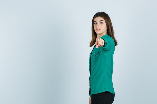 Junge frau, die auf kamera im grünen hemd zeigt und ernst schaut. .