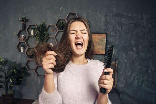 Junge frau, die auf kamm mit haaren, entsetzen und wutanfall, haarprobleme schaut