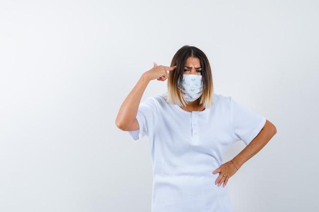 Junge frau, die auf kopf zeigt, während sie in t-shirt, maske finster blickt und verwirrt aussieht. vorderansicht.