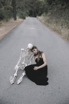 Junge frau, die auf leerer straße im wald mit dem skelett sitzt