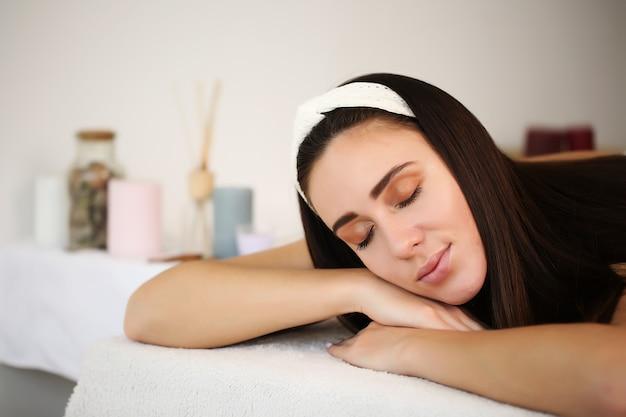 Junge frau, die auf massagebett im spa- und wellnesscenter liegt.