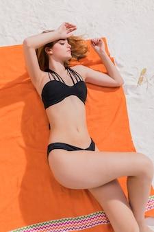 Junge frau, die auf orange tuch liegt