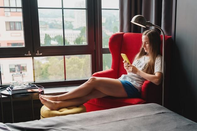 Junge frau, die auf rotem sessel nahe dem fenster sitzt und auf ihrem smartphone tippt