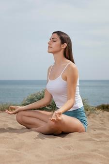 Junge frau, die auf sand meditiert
