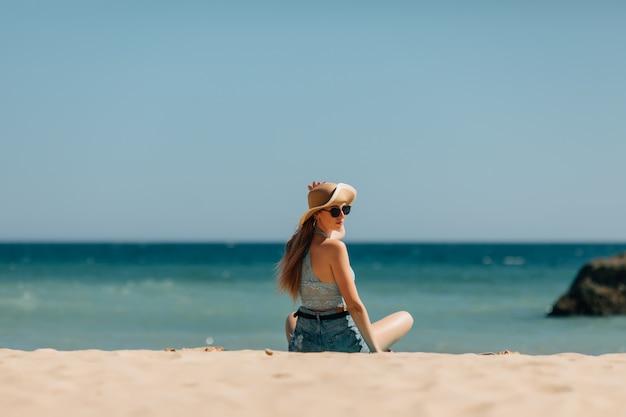 Junge frau, die auf sand sitzt und zu einem meer schaut. rückansicht