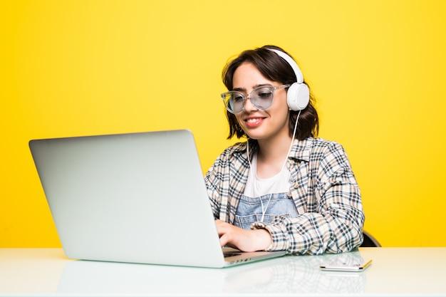 Junge frau, die auf schreibtisch mit laptop lokalisiert arbeitet