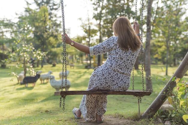 Junge frau, die auf schwingen allein im park sitzt.