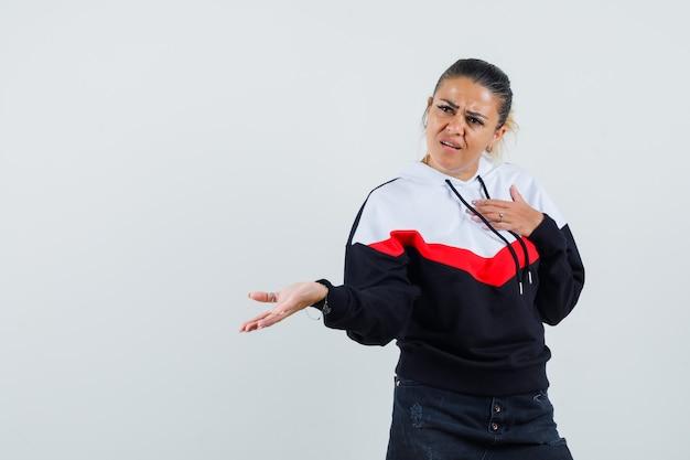 Junge frau, die auf sich zeigt, während sie offene handfläche in buntem sweatshirt beiseite spreizt und aggressive vorderansicht sieht.