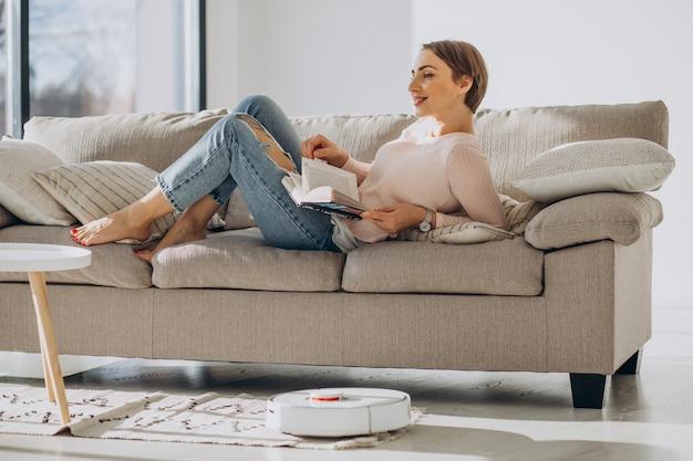 Junge frau, die auf sofa liegt und ein buch liest, während roboterstaubsauger hausarbeit macht