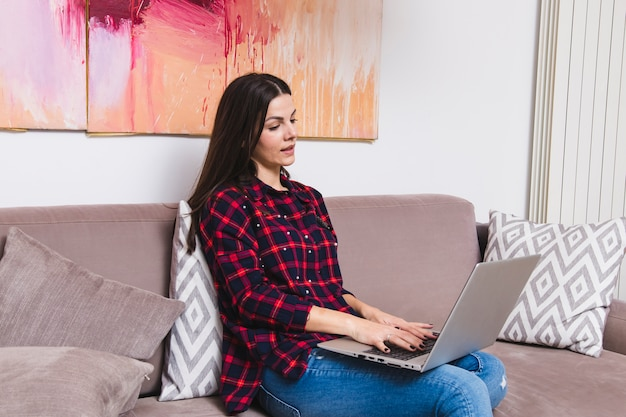 Junge frau, die auf sofa unter verwendung des laptops sitzt