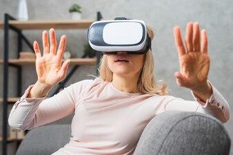 Junge Frau, die auf Sofaerfahrung mit virtueller Realität sitzt