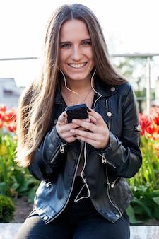Junge frau, die auf steinbrüstung sitzt, smartphone hält und musik in den kopfhörern hört
