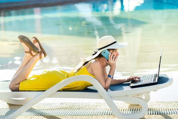 Junge frau, die auf strandstuhl liegt und an computer-laptop arbeitet, der mit drahtlosem internet verbunden ist und gespräch auf mobilem sellphone im sommerresort führt. geschäfte machen während des reisekonzepts.