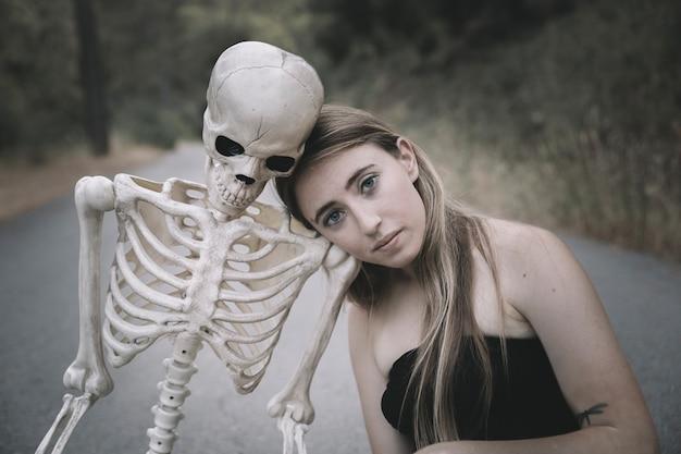 Junge frau, die auf straße mit dem skelett sitzt