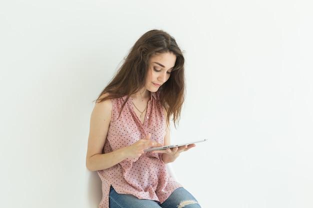 Junge frau, die auf stuhl sitzt, der mit einer tablette auf weißer wand arbeitet