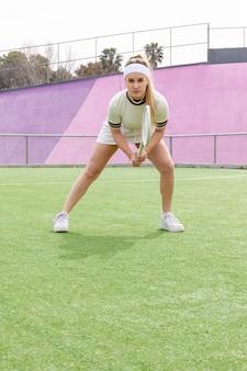 Junge frau, die auf tennismatch sich konzentriert