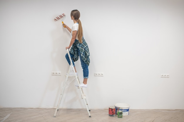 Junge frau, die auf trittleiter steht und wände malt