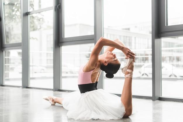 Junge frau, die auf übendem ballett des bodens ballett im tanzstudio sitzt