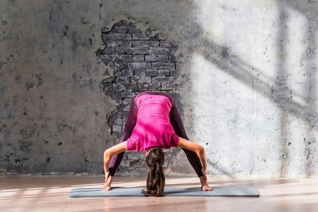 Junge frau, die auf übendem yoga der übungsmatte steht