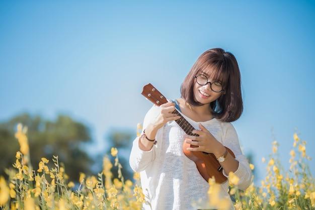 Junge frau, die auf ukulele auf sunhemp hintergrund spielt