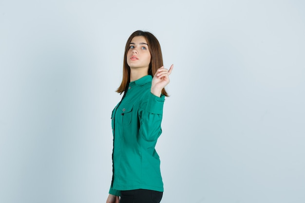 Junge frau, die aufwirft, während sie im grünen hemd zurück zeigt und zuversichtlich schaut.