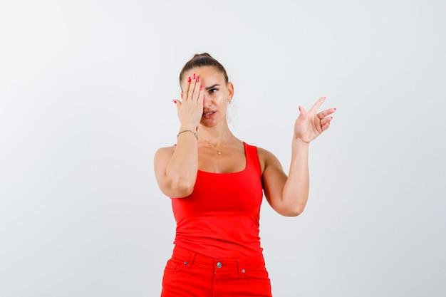 Junge frau, die augen bedeckt, zeigt in rotem trägershirt, hosen und schaut unglücklich, vorderansicht.