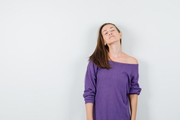 Junge frau, die augen im violetten hemd geschlossen hält und friedlich aussieht. vorderansicht.