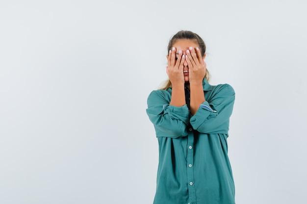 Junge frau, die augen mit händen in der grünen bluse bedeckt und müde schaut