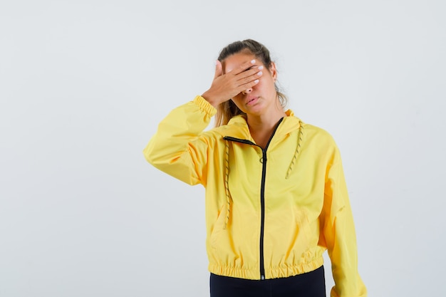 Junge frau, die augen mit hand im gelben regenmantel bedeckt und gelangweilt schaut
