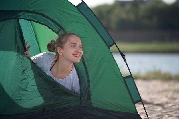 Junge frau, die aus dem touristischen zelt herausschaut und lächelt. morgen auf dem campingplatz.