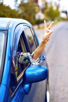 Junge frau, die auto auf dem land fährt, legte ihre hand aus dem auto, genießt ihre freiheit, macht gute yo wissenschaft durch ihre hand, reiseurlaubskonzept.
