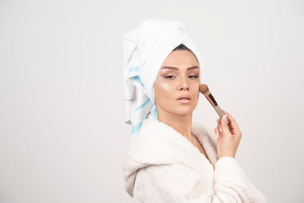 Junge frau, die bademantel und handtuch trägt, verwenden quaste für make-up