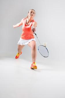 Junge frau, die badminton auf weiß spielt