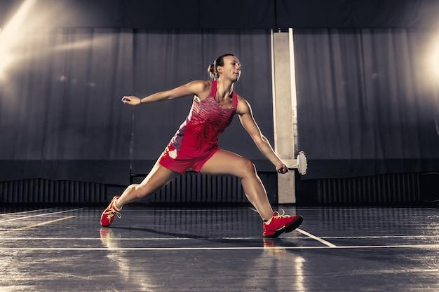 Junge frau, die badminton im fitnessstudio spielt