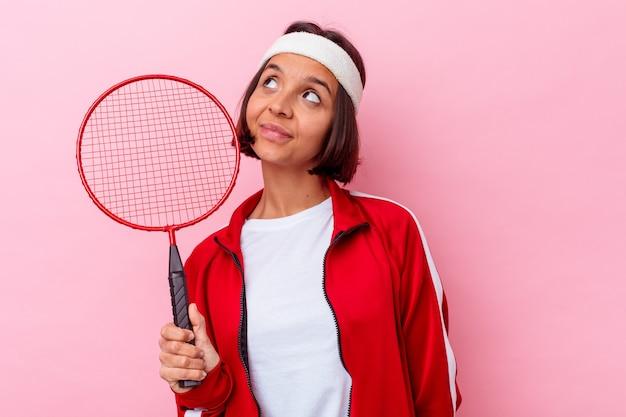 Junge frau, die badminton spielt, isoliert auf rosa wand träumt davon, ziele und zwecke zu erreichen
