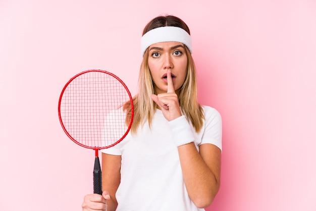 Junge frau, die badminton spielt, isolierte isoliert ein geheimnis oder bat um stille.