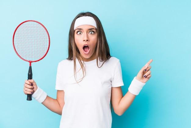 Junge frau, die badminton spielt, zeigt isoliert zur seite