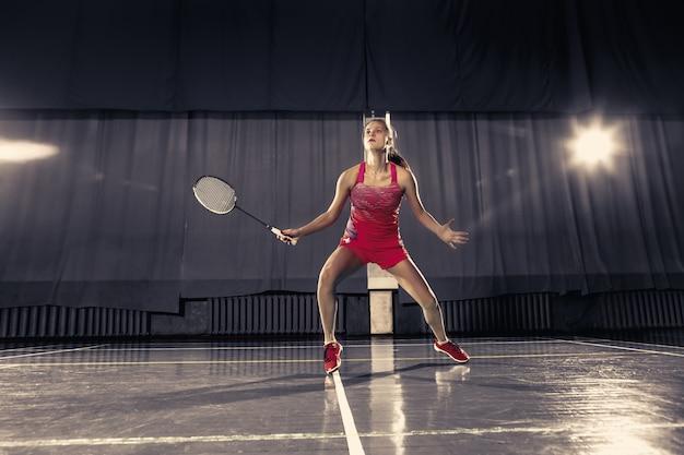 Junge frau, die badminton über turnhalle spielt