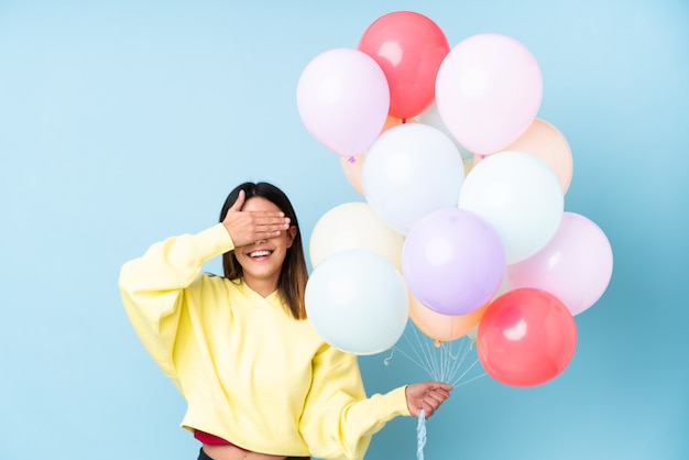 Junge frau, die ballone über lokalisierter wand hält