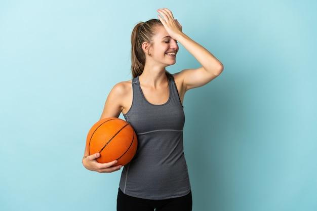 Junge frau, die basketball auf blau isoliert spielt, hat etwas realisiert und beabsichtigt die lösung