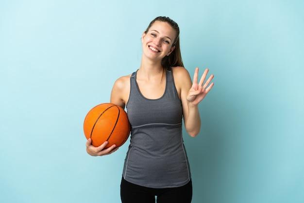 Junge frau, die basketball lokalisiert auf blau glücklich spielt und vier mit den fingern zählt