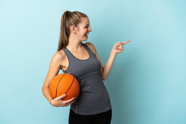Junge frau, die basketball lokalisiert auf blau zeigendem finger zur seite spielt und ein produkt präsentiert