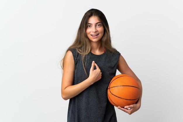 Junge frau, die basketball lokalisiert mit überraschtem gesichtsausdruck spielt