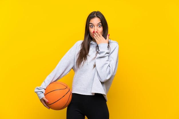 Junge frau, die basketball mit überraschungsgesichtsausdruck spielt