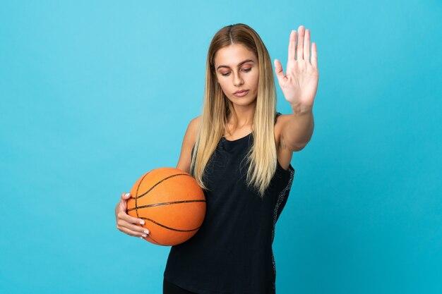 Junge frau, die basketball spielt, isolierte stoppgeste und enttäuscht