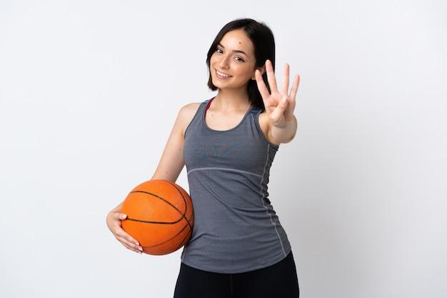 Junge frau, die basketball spielt, lokalisiert auf weißem hintergrund glücklich und zählt vier mit den fingern