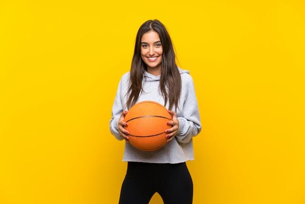 Junge frau, die basketball spielt